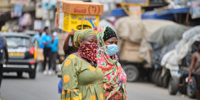 Two Ghanaian women wearing nose masks and handkerchiefs.